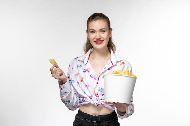 Vooraanzicht jonge mooie vrouwelijke aardappel cips te houden en glimlachend op wit oppervlak