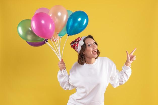 Vooraanzicht jonge mooie vrouwelijke bedrijf ballonnen op gele kerst vrouw nieuwjaar kleur emotie