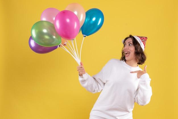 Vooraanzicht jonge mooie vrouwelijke bedrijf ballonnen op gele kerstmis nieuwjaar kleur vrouw emotie