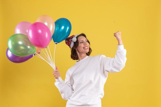 Vooraanzicht jonge mooie vrouwelijke bedrijf ballonnen op gele kleur kerstmis nieuwjaar emotie vrouw