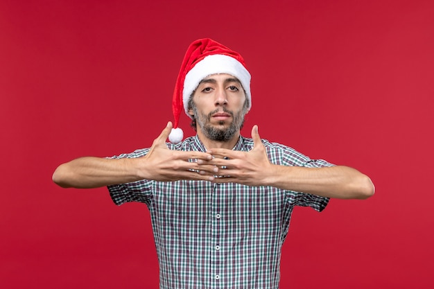 Vooraanzicht jonge persoon met nieuwe jaar dop op de rode muur rode nieuwe jaar vakantie man