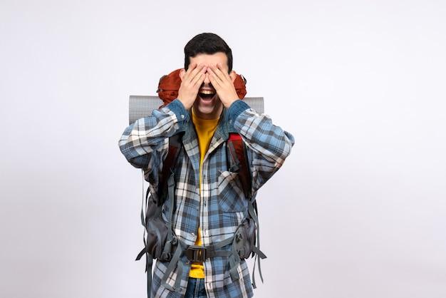Vooraanzicht jonge reiziger man met rugzak voor ogen met handen