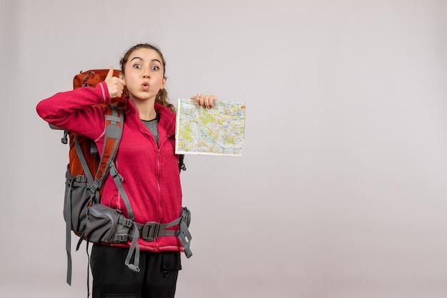 Vooraanzicht jonge reiziger met grote rugzak die duimen omhoog tekenkaart maakt