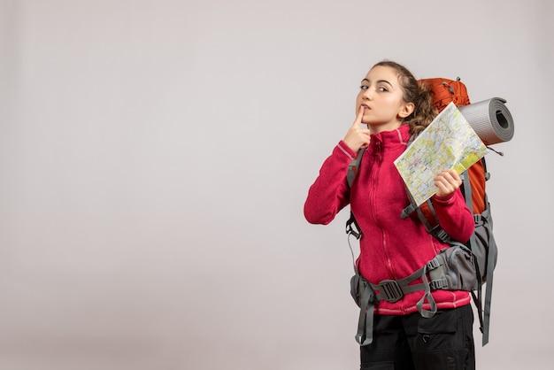Vooraanzicht jonge reiziger met grote rugzak die kaart omhoog houdt en vinger op haar mond legt
