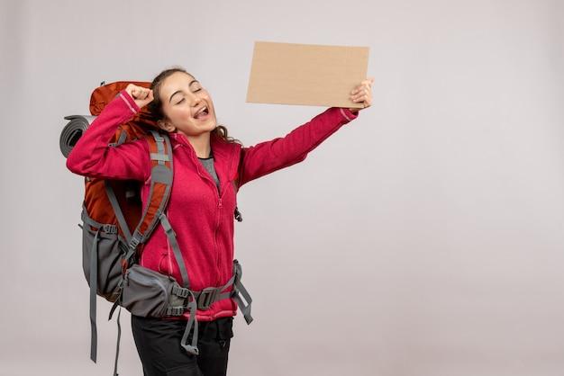 Vooraanzicht jonge reiziger met grote rugzak die karton omhoog houdt