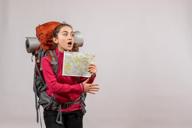 Vooraanzicht jonge reiziger met grote rugzak met kaart die hand geeft
