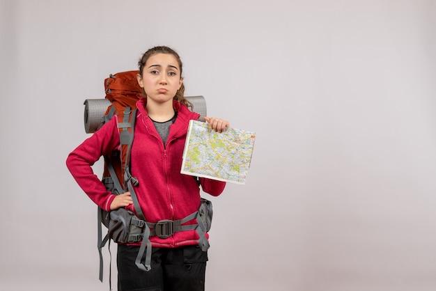Vooraanzicht jonge reiziger met grote rugzak met kaart die hand op een taille legt