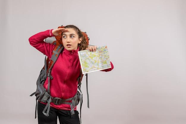 Vooraanzicht jonge reiziger met grote rugzak met kaart die naar iets kijkt