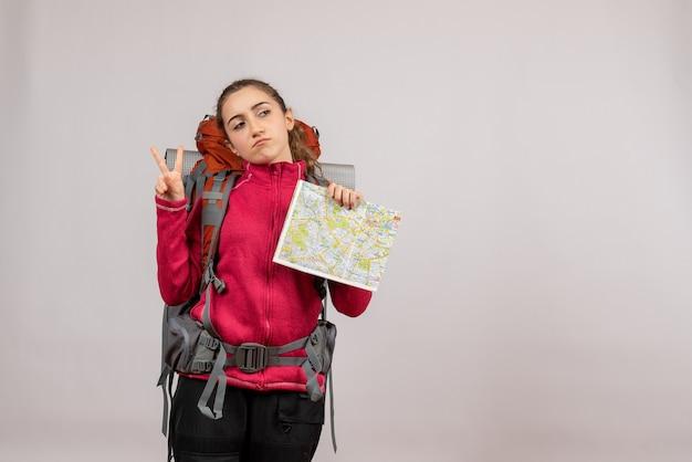 Vooraanzicht jonge reiziger met grote rugzak met kaart die overwinningsteken maakt