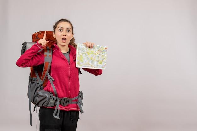 Vooraanzicht jonge reiziger met grote rugzak met kaart wijzende vinger omhoog