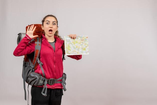 Vooraanzicht jonge reiziger met grote rugzak met kaart zwaaiende hand