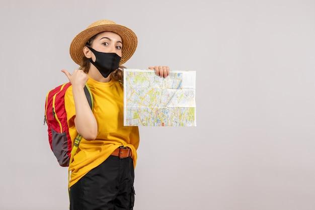 Vooraanzicht jonge reiziger met rode rugzak die kaart omhoog houdt en duimen omhoog geeft