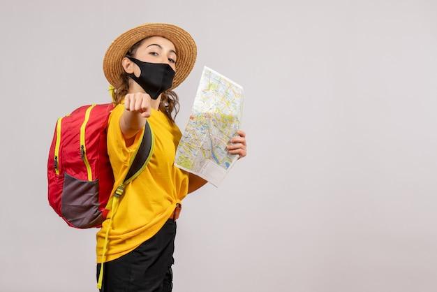 Vooraanzicht jonge reiziger met rode rugzak die kaart omhoog houdt