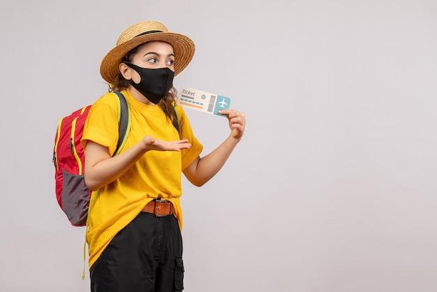 Vooraanzicht jonge reiziger met rode rugzak die reiskaartje omhoog houdt