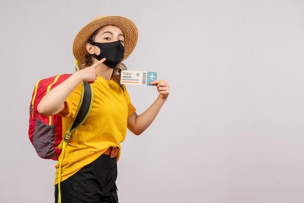 Vooraanzicht jonge reiziger met rode rugzak die ticket omhoog houdt