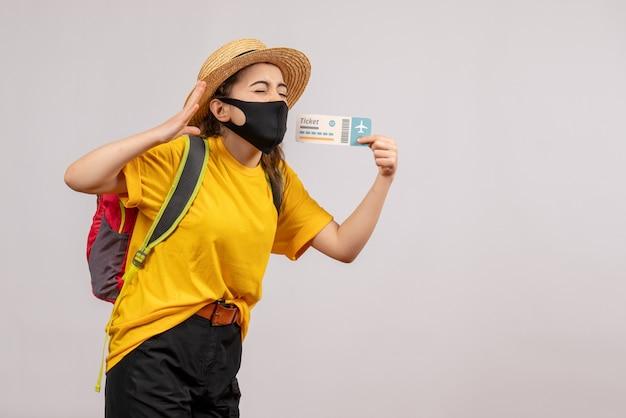 Vooraanzicht jonge reiziger met rugzak die de ogen van het ticket omhoog houdt