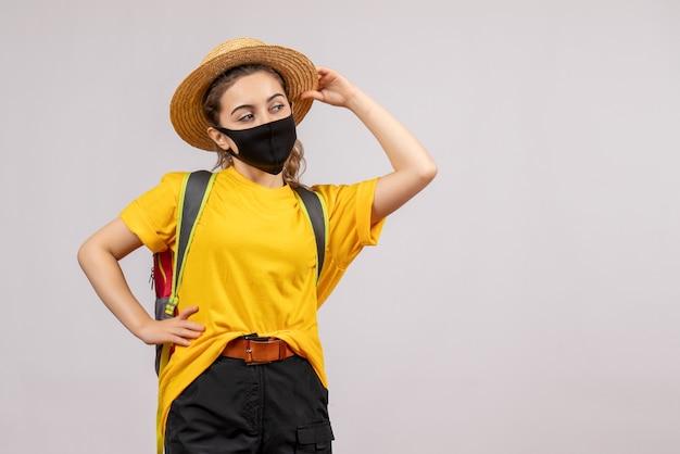 Vooraanzicht jonge reiziger met rugzak die haar panama vasthoudt