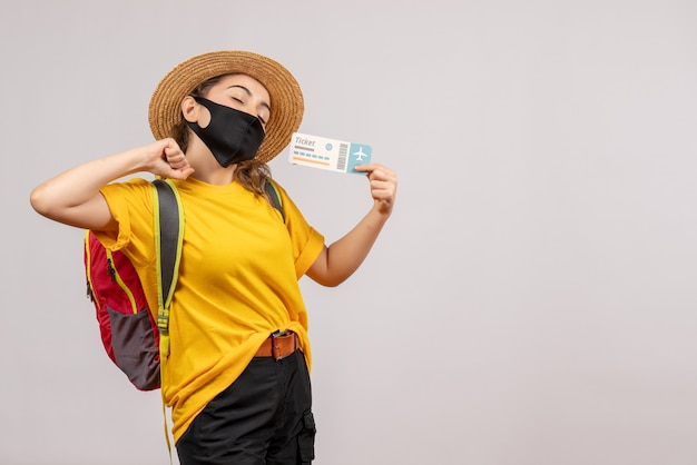 Vooraanzicht jonge reiziger met rugzak die het uitrekken van het ticket omhoog houdt