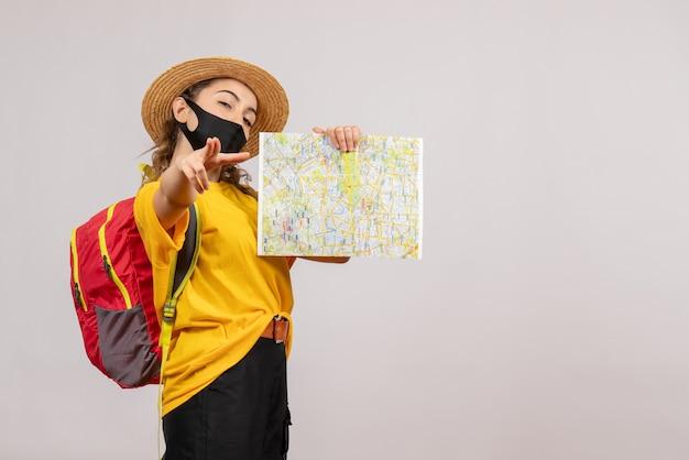 Vooraanzicht jonge reiziger met rugzak die kaart omhoog houdt die naar voren wijst