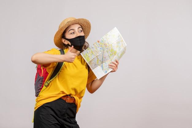 Vooraanzicht jonge reiziger met rugzak die kaart omhoog houdt en duimen omhoog geeft