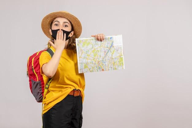 Vooraanzicht jonge reiziger met rugzak die kaart omhoog houdt en hand op haar mond legt