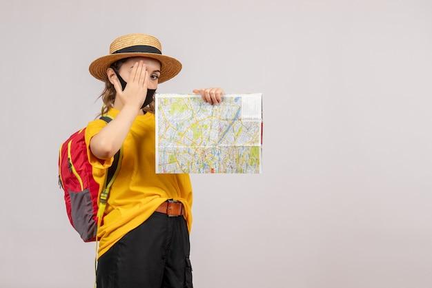 Vooraanzicht jonge reiziger met rugzak die kaart omhoog houdt en hand op haar oog legt