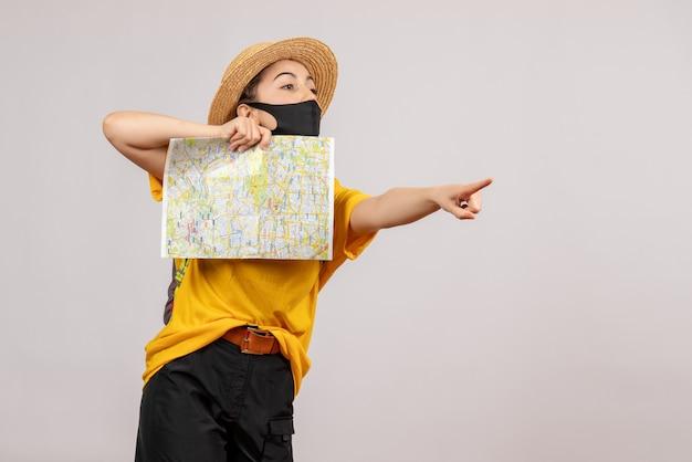 Vooraanzicht jonge reiziger met rugzak die kaart omhoog houdt wijzend op iets