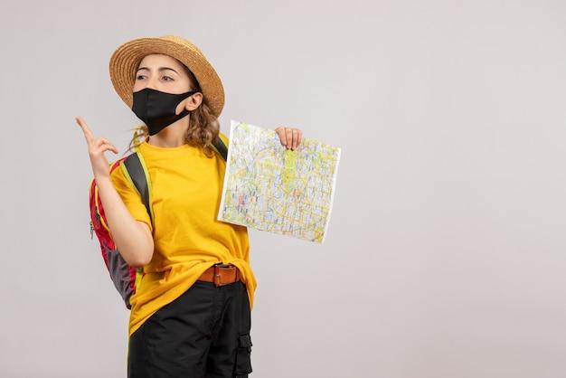 Vooraanzicht jonge reiziger met rugzak die kaart omhoog houdt