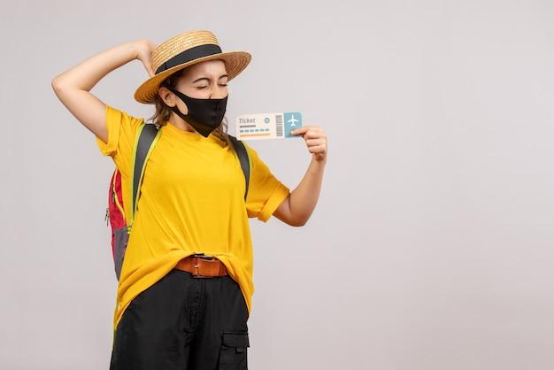 Vooraanzicht jonge reiziger met rugzak die reiskaartje omhoog houdt