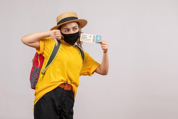 Vooraanzicht jonge reiziger met rugzak die ticket omhoog houdt en duim omlaag tekent