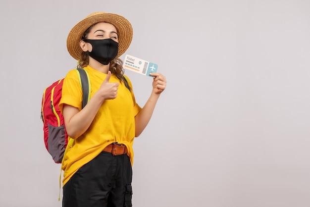 Vooraanzicht jonge reiziger met rugzak die ticket omhoog houdt en duimen omhoog tekent