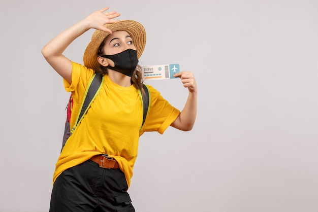 Vooraanzicht jonge reiziger met rugzak die ticket omhoog houdt en iemand aanroept