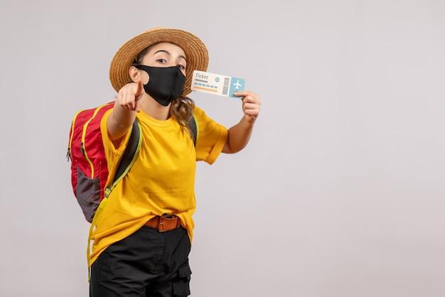 Vooraanzicht jonge reiziger met rugzak die ticket omhoog houdt en naar voren wijst