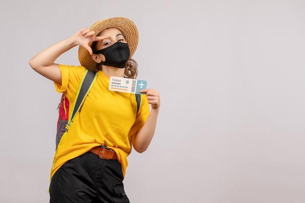 Vooraanzicht jonge reiziger met rugzak die ticket staande houdt