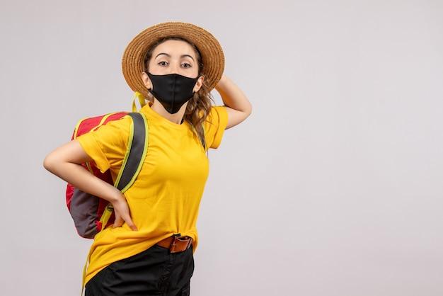 Vooraanzicht jonge reiziger met rugzak hand op een taille zetten