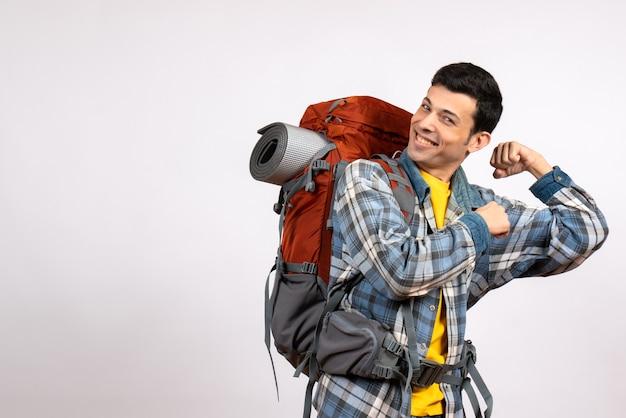 Vooraanzicht jonge reiziger met rugzak met armspier