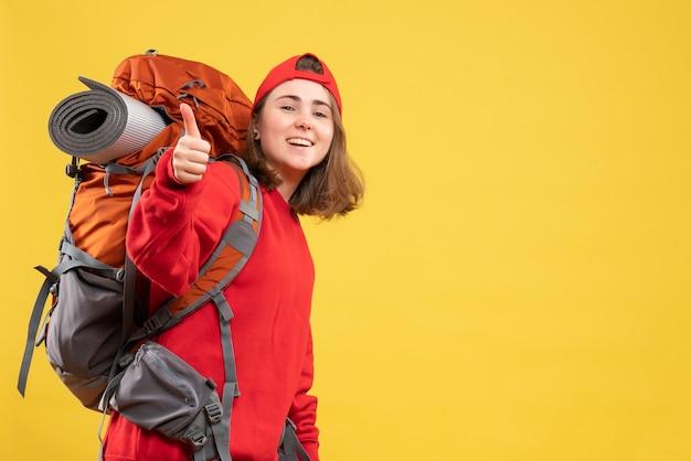 Vooraanzicht jonge reizigersvrouw in rode rugzak die duim opgeeft