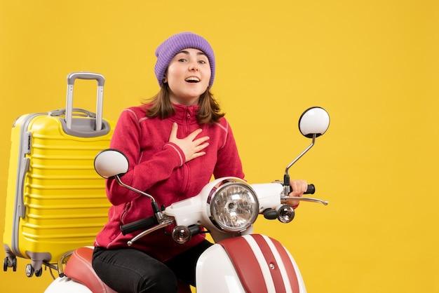 Vooraanzicht jonge reizigersvrouw in vrijetijdskleding op bromfiets