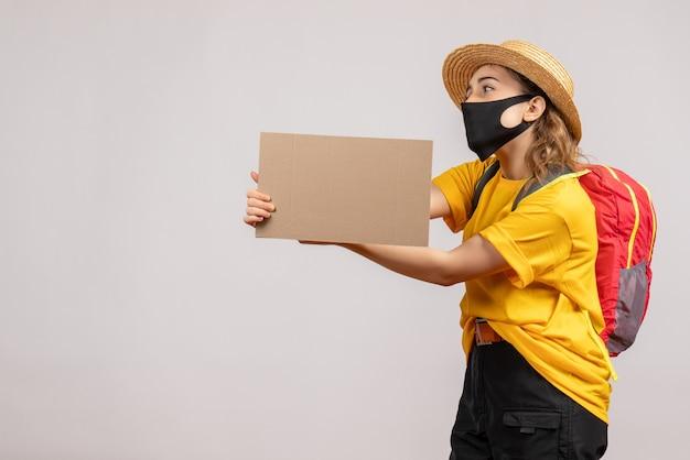 Vooraanzicht jonge reizigersvrouw met rugzak die karton houdt