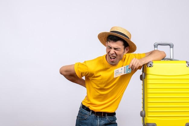 Vooraanzicht jonge toerist die zich dichtbij gele koffer bevindt die zijn rug met pijn houdt