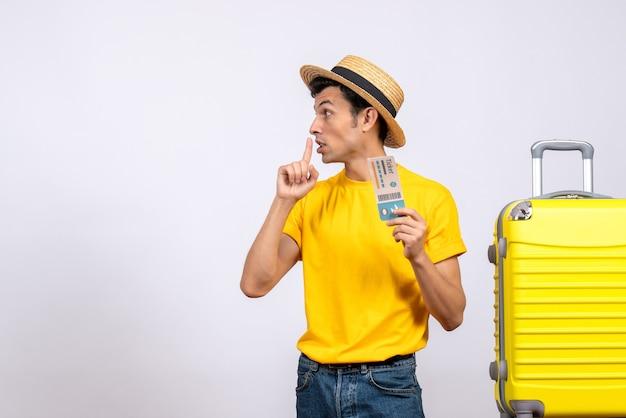 Vooraanzicht jonge toerist in geel t-shirt staande in de buurt van gele koffer stilte teken maken