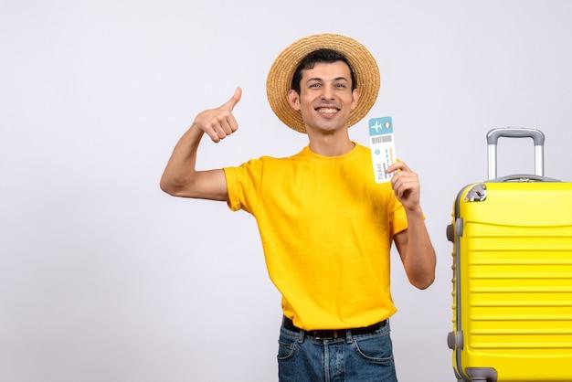 Vooraanzicht jonge toerist in gele t-shirt staande in de buurt van gele koffer duim opgevend teken houden vliegticket