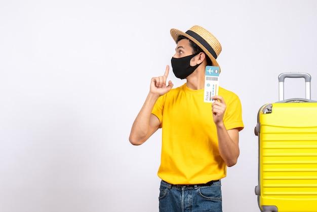 Vooraanzicht jonge toerist met strohoed die zich dichtbij het gele vliegticket van de kofferholding bevindt