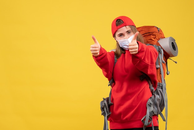 Vooraanzicht jonge toerist met toeristenrugzak en masker die duimen opgeeft