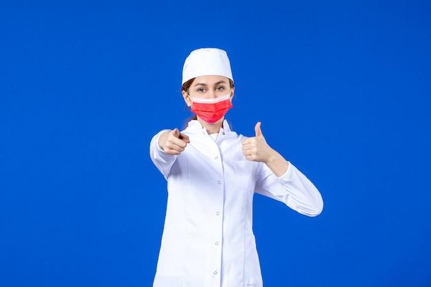 Vooraanzicht jonge verpleegster in medisch pak met rood beschermend masker op blauwe muur