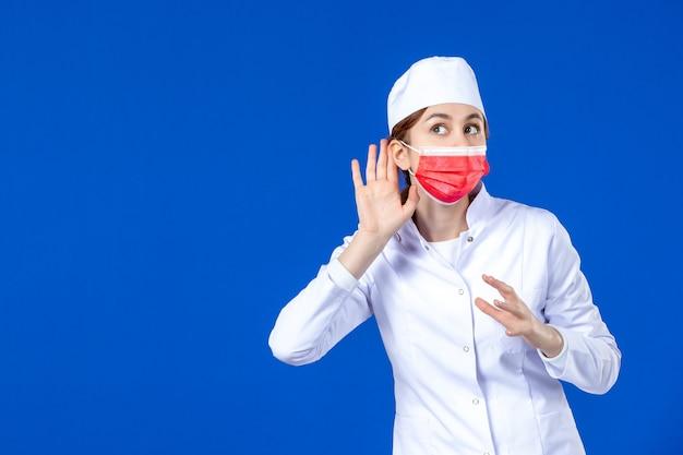 Vooraanzicht jonge verpleegster in medisch pak met rood masker op blauwe muur