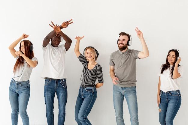 Vooraanzicht jonge vrienden met koptelefoon dansen