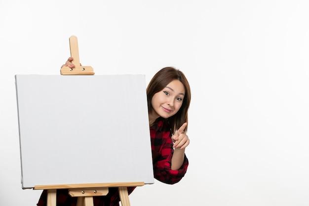Vooraanzicht jonge vrouw achter ezel om op een witte muur te tekenen