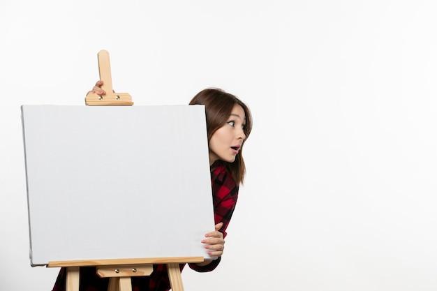 Vooraanzicht jonge vrouw achter ezel voor het tekenen op witte muurschildering kunst teken kwast kunstenaar kleur