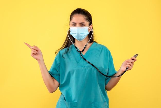 Vooraanzicht jonge vrouw arts in uniform wijzend op iets staande op gele achtergrond